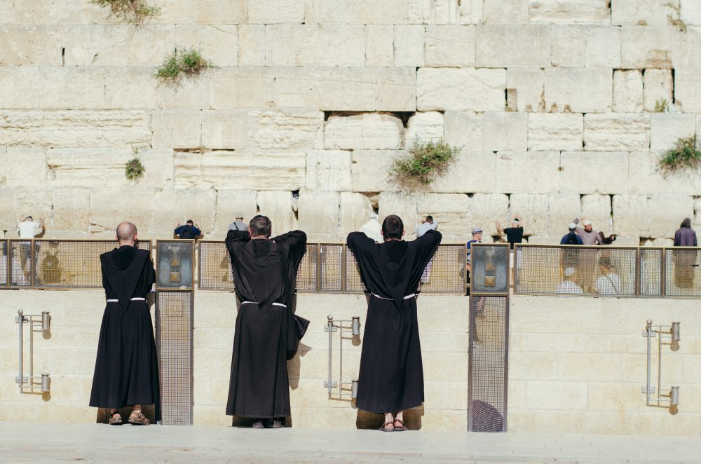 I love this photo of these monks watching visitors to the Wall.